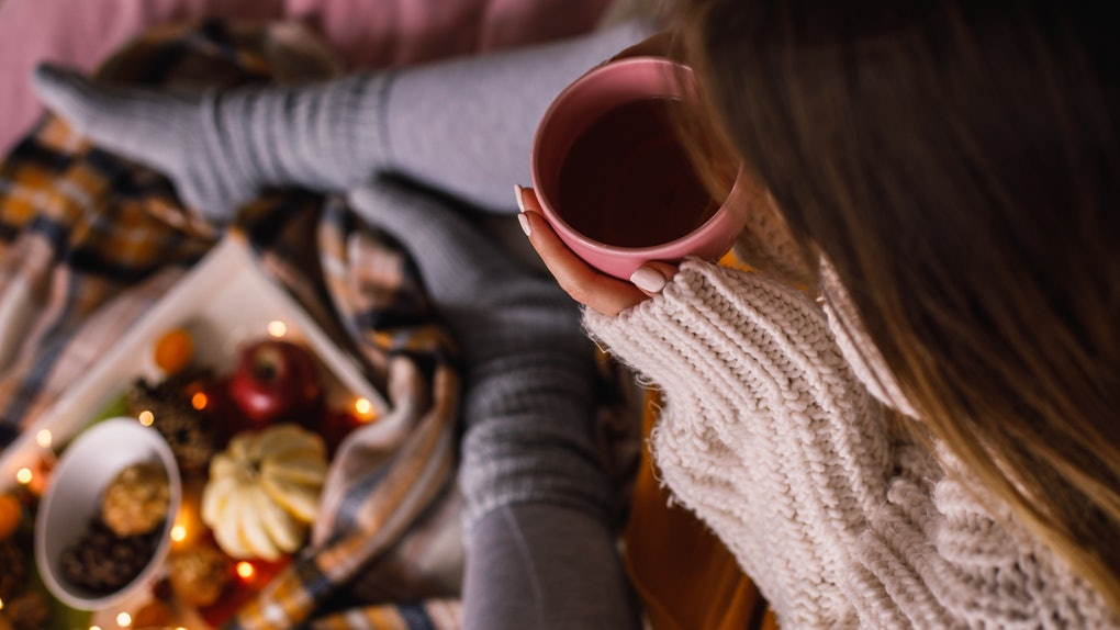 A woman wearing leggings and a cozy sweater sips a cup of tea on her bed while enjoying afternoon tea.