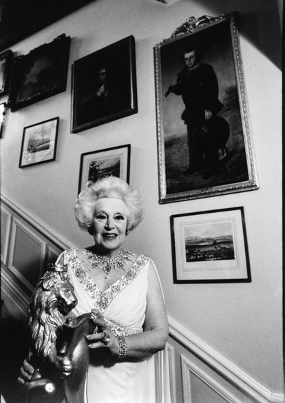 Dame Barbara Cartland (1901-2000) English author of romance novels, on the staircase of her home in ...