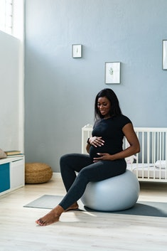 Image of a pregnant person, sitting in a nursery atop an exercise ball.