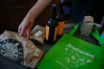 A Bi-Rite clerk bags the groceries of Instacart personal shopper, Sydney Hollingsworth, who was fill...