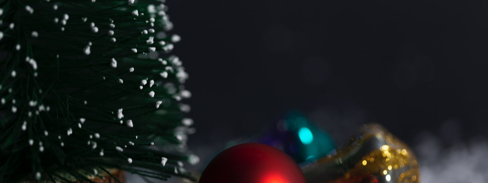 Christmas tree with Christmas decoration and Christmas light against snow  black background