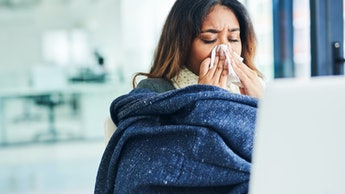 Shot of a young businesswoman blowing her nose with a tissue and covering with a blanket in a modern...
