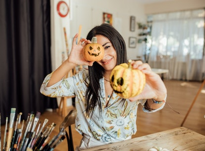 Young woman holding Jack O' Lanterns in her hand for Halloween