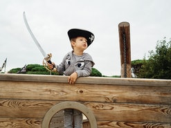 Little boy wearing a pirate hat and smiling inside a pirate ship and holding a sword. Childhood conc...