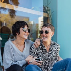 Two friends hang out on a step. Experts share what to say to someone who's just come out and support...