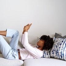 A woman in light blue jeans brainstorms Instagram photo dump caption ideas.