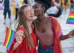 Young pretty women meeting at the pride parade event, hugging and kissing
