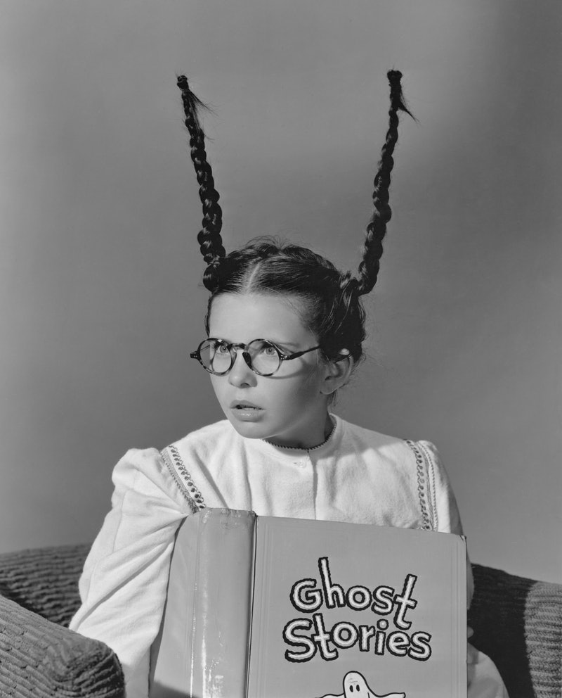 A girl reading ghost stories with her pigtails standing on end. These creepy ghost story podcasts ar...
