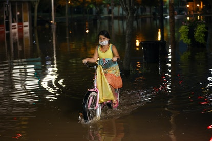 NEW JERSEY, USA - SEPTEMBER 2: A girl rides a bike on the flooded street in the Town of Bound Brook ...