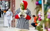 VANCOUVER, BRITISH COLUMBIA - DECEMBER 24: An employee of Foot Locker dressed as Grinch is seen posi...