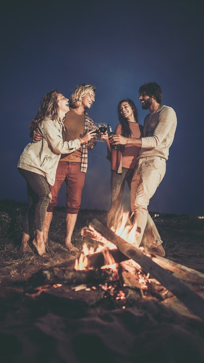 Friends having fun while toasting by the bonfire on the beach at night.