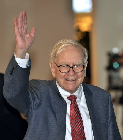 US billionaire Warren Buffett waves upon his arrival at Tokyo's Haneda airport for a visit to Japan ...