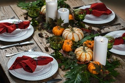 Autumn dinner. Autumn decor, white candles, autumnal leaves, white porcelain on a wooden table.