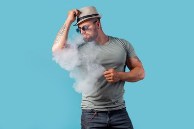 Bearded male in hat and sunglasses smoking a vapor cigarette as an alternative to tobacco. Studio sh...