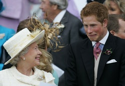 Britain's Queen Elizabeth II and Prince Harry share a joke as they watch Prince Charles and his brid...