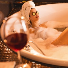 Relaxed woman with facial mask enjoying in bathtub.