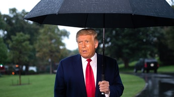 US President Donald Trump holds an umbrella as he speaks to the media under the rain prior to depart...