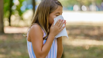 Photo of a Girl With Flu in Public Park Using Facial Tissues While Sneezing Due to Seasonal Flu or R...