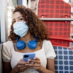 A woman wearing a mask texts a new friend while riding a bus. Here's how to get to know someone over...
