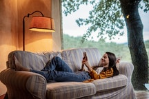 A woman lies on a '70s style sofa switching her professional Instagram account back to personal.