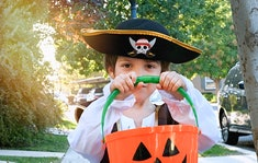 Pensive smiling little boy wearing a halloween pirate costume looking at the camera holding a Jack o...