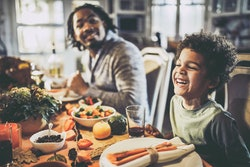 Happy African American boy enjoying while having Thanksgiving lunch with his father at dining table.