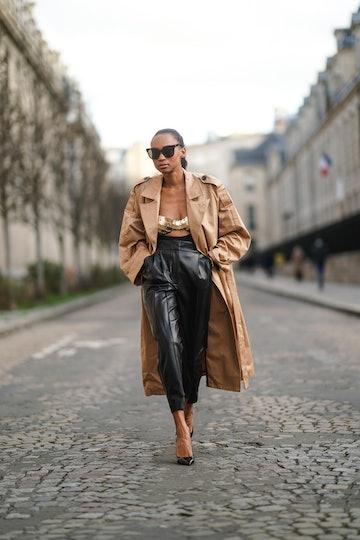 PARIS, FRANCE - FEBRUARY 17: Emilie Joseph wears sunglasses, golden earrings, a beige trench coat fr...
