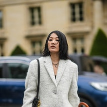 PARIS, FRANCE - OCTOBER 05: A guest wears a silver large chain pendant necklace, a white fluffy long...
