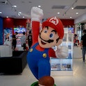 TIANJIN, CHINA - 2021/07/20: A cartoon figurine of Super Mario Bros. stands in front of a Nintendo S...