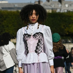 Lace-trimmed corset over white blouse in Spring/Summer 2022 street style.