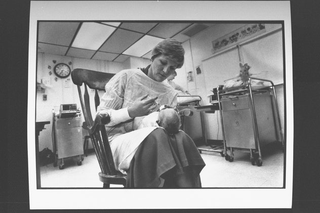 A head nurse feeds a drug-addicted baby in a maternity ward.