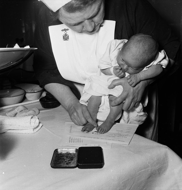 A nurse stamps the footprint of a baby in a vintage maternity ward.