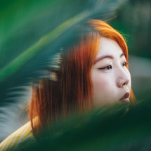 A woman with red hair looks out behind plants. These are Ophiuchus' biggest strengths, according to ...