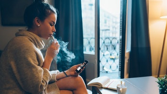 Young girl at home smoking electronic cigarette and online banking on mobile phone