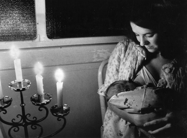 A mother nurses her baby during a blackout.