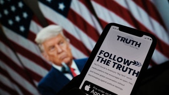 """TOPSHOT - This illustration photo shows a person checking the app store on a smartphone for """"Truth S..."""