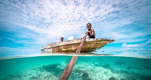 Split wide angle shot of Bajau Children rowing a wooden canoe in the ocean at a tropical island beac...
