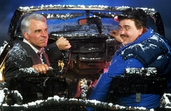 Steve Martin and John Candy sit in a destroyed car in a scene from the film 'Planes, Trains & Automo...