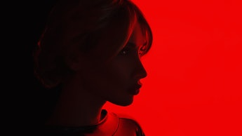 Studio Portrait a young blonde transgender woman in latex on a red glowing background