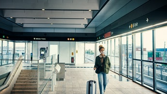 Shot of a masked young woman travelling through a subway station