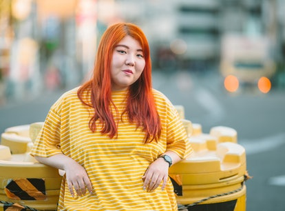 A young millennial generation woman is wearing a yellow t-shirt in the city.