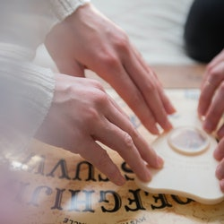 Young women use a Ouija board. The Ouija board's history and origins reveal much about the talking b...