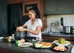 Skilled female sushi chef, making the rice balls for the Nigiri, in her modern domestic kitchen