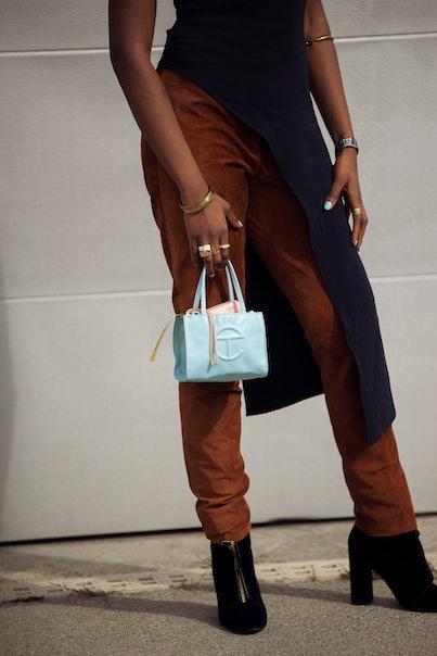 COPENHAGEN, DENMARK - AUGUST 11: Guest wearing brown pants and navy blue long top and light blue bag...