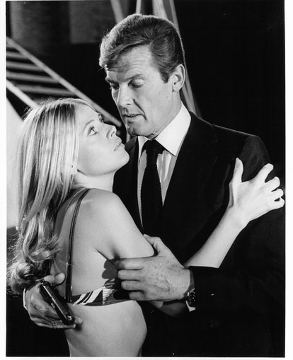 Roger Moore holds a gun as he embraces Britt Ekland who is wearing a bikini top in a scene from the ...
