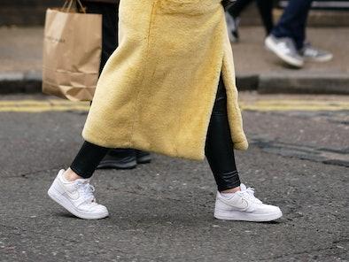 LONDON, ENGLAND - JANUARY 05: A guest wears a gold earrings, a black shiny leather crocodile pattern...