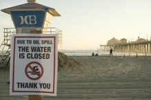 HUNTINGTON BEACH, CALIFORNIA - OCTOBER 03: A warning sign is posted near oil washed up on Huntington...