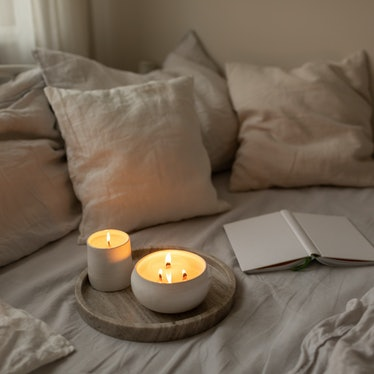 Organic soya wax candles with wooden candlewick in white ceramic bowls on linen bedding set with boo...