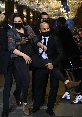 A demonstrator is being evicted by security members as models present a creation by Louis Vuitton du...