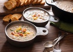 A bowl of TikTok's viral crockpot potato soup with bacon, cheddar cheese, and chives sits on the cou...